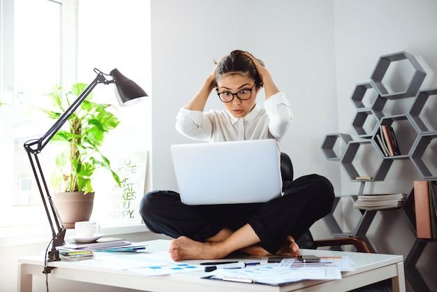 Belle jeune femme d'affaires assis sur une table avec ordinateur portable sur le lieu de travail.