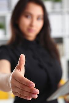 Belle jeune femme d'affaires brune donne la main devant