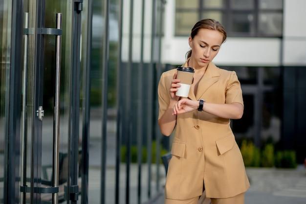 Belle jeune femme d'affaires caucasienne mignonne avec une tasse de café, utilisant un téléphone portable et buvant du café en souriant