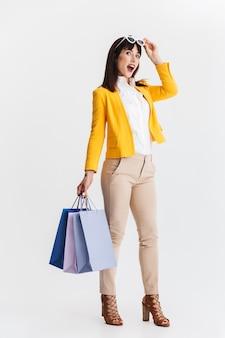 Belle jeune femme d'affaires choquée posant isolée sur un mur blanc tenant des sacs à provisions.