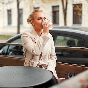 Belle jeune femme d'affaires dans un manteau, boire du café à l'extérieur