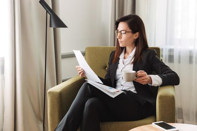 Belle jeune femme d'affaires dans des vêtements de cérémonie à l'intérieur à la maison en buvant du café avec des documents.