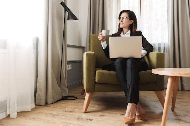 Belle jeune femme d'affaires dans des vêtements de cérémonie à l'intérieur à la maison travailler avec un ordinateur portable en buvant du café.