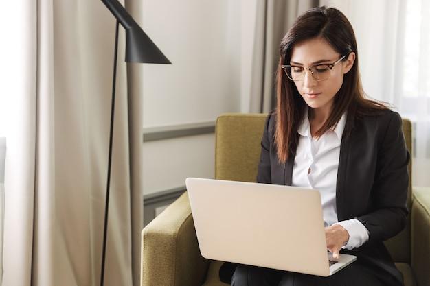 Belle jeune femme d'affaires dans des vêtements de cérémonie à l'intérieur à la maison travailler avec un ordinateur portable.