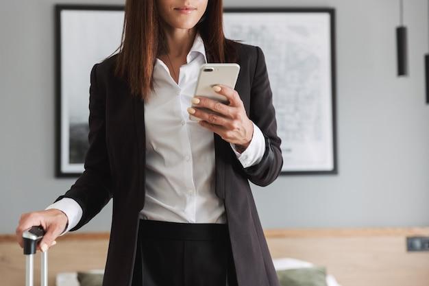 Belle jeune femme d'affaires dans des vêtements de cérémonie à l'intérieur à la maison avec une valise à l'aide d'un téléphone portable.
