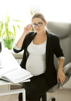 Belle jeune femme d'affaires enceinte parlant au téléphone sur le lieu de travail