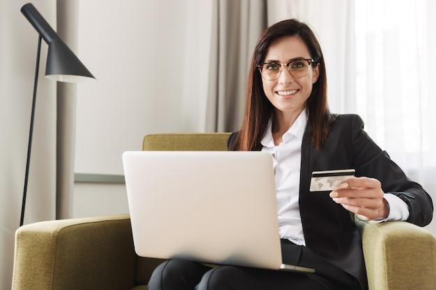 Belle jeune femme d'affaires heureuse dans des vêtements de cérémonie à l'intérieur à la maison travailler avec un ordinateur portable tenant une carte de crédit.