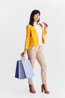 Belle jeune femme d'affaires heureuse posant isolée sur mur blanc tenant des sacs à provisions.