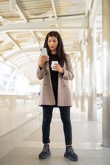 Belle jeune femme d'affaires indienne à l'aide de téléphone et prendre un café sur le pouce en ville