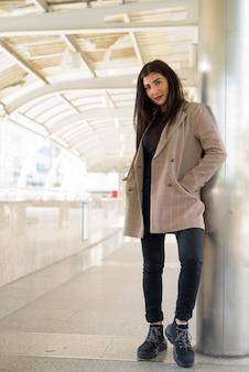 Belle jeune femme d'affaires indienne à la passerelle de la ville