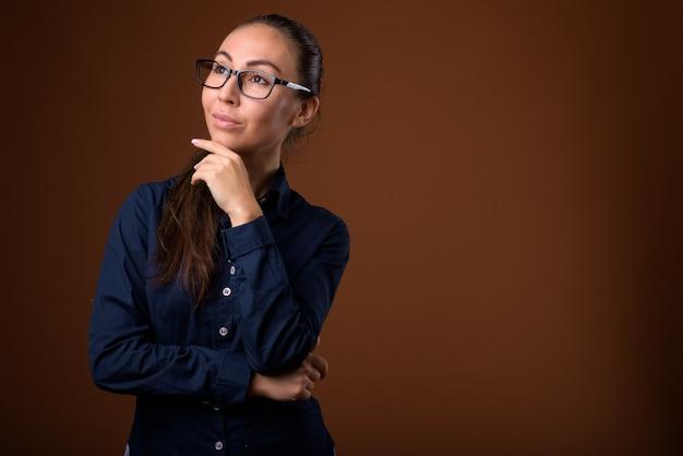Belle jeune femme d'affaires portant des lunettes sur fond marron