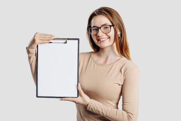 Belle jeune femme d'affaires portant des lunettes tient un presse-papiers avec une maquette d'espace vide isolé sur fond gris. atteindre le concept d'entreprise de richesse de carrière. couverture d'apprentissage en ligne