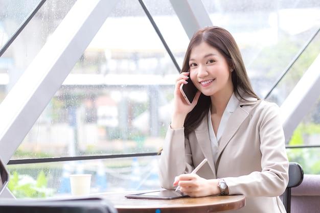 Belle jeune femme d'affaires professionnelle asiatique dans un costume de couleur crème regardant la caméra tient un smartphone pour parler, discuter et enregistrer des informations joyeusement sur une tablette dans un café.