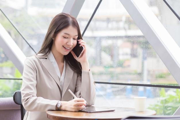 Belle jeune femme d'affaires professionnelle asiatique dans un costume de couleur crème tient un smartphone pour parler, discuter et enregistrer des informations joyeusement sur une tablette dans un café.