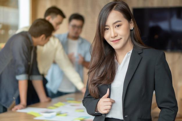 Belle jeune femme d'affaires réussie debout dans la salle de réunion