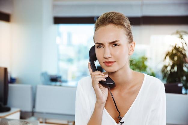 Belle jeune femme d'affaires réussie, parlant au téléphone, sur le bureau