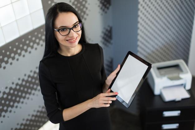 Belle jeune femme d'affaires en robe noire et lunettes détiennent classeur et tablette