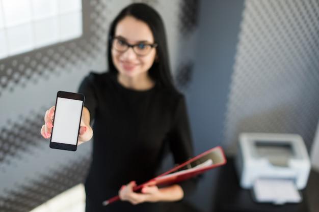 Belle jeune femme d'affaires en robe noire et lunettes détiennent dossier papier et show téléphone