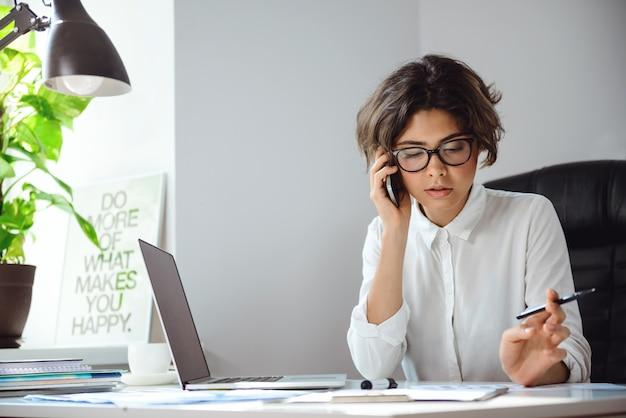 Belle jeune femme d'affaires, s'exprimant au téléphone sur le lieu de travail au bureau.