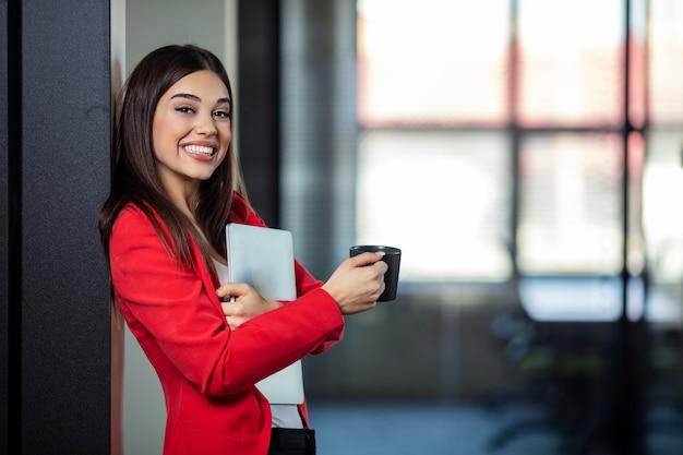 Belle jeune femme d'affaires souriant et tenant un ordinateur portable et une tasse de café.