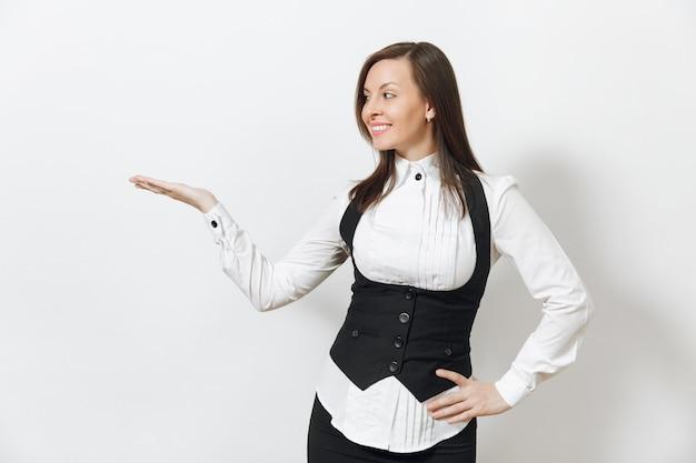Belle jeune femme d'affaires souriante aux cheveux bruns en costume noir, chemise blanche, pointant la main droite de côté isolé sur mur blanc