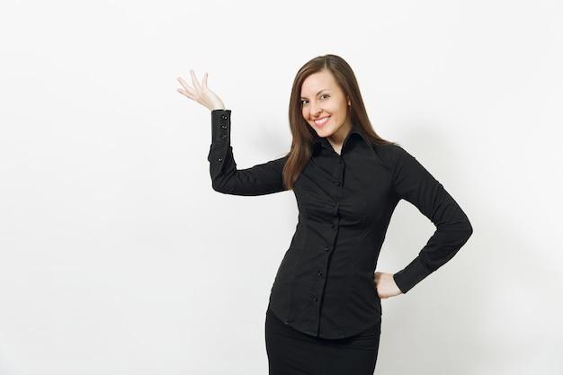 Belle jeune femme d'affaires souriante caucasienne aux cheveux bruns en chemise classique noire et jupe pointant la main de côté isolée sur mur blanc