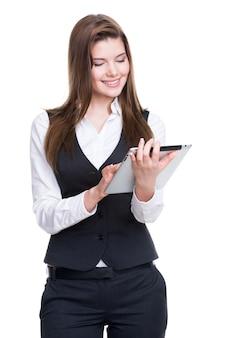 Belle jeune femme d'affaires souriante dans un costume gris à l'aide de tablette sur fond blanc.