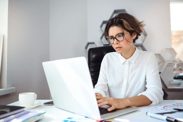 Belle jeune femme d'affaires travaillant avec ordinateur portable sur le lieu de travail au bureau.