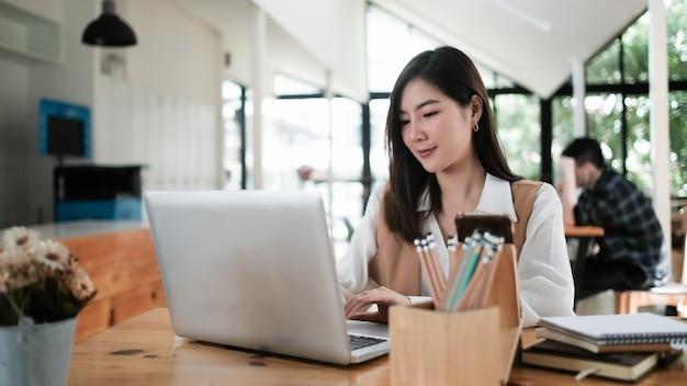 Belle jeune femme d'affaires travaillant sur son projet avec ordinateur portable dans la salle de réunion.