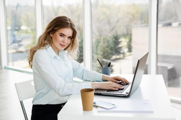 Belle jeune femme d'affaires travaille au bureau avec un ordinateur portable. notion de réussite