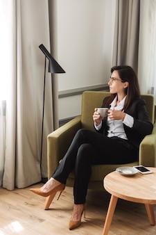Belle jeune femme d'affaires en vêtements de cérémonie à l'intérieur à la maison en buvant du café.