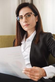 Belle jeune femme d'affaires vêtue de vêtements de cérémonie à l'intérieur à la maison travaille avec des documents et des graphiques.