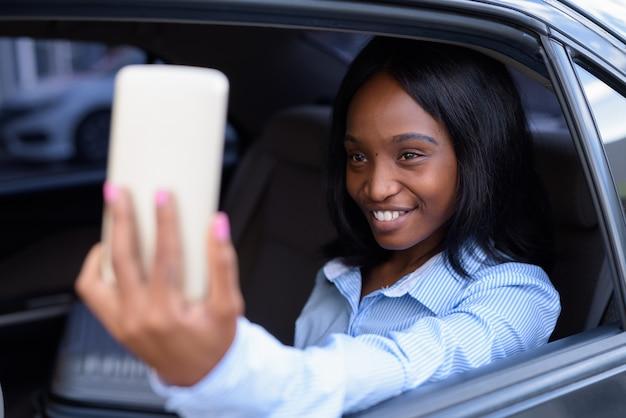 Belle jeune femme d'affaires zoulou africaine à l'intérieur de la voiture