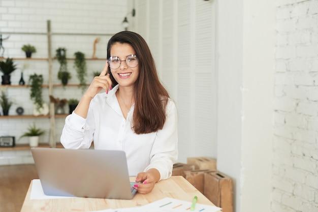 Une belle jeune femme afghane est assise devant une table devant un ordinateur portable avec des tableaux et des graphiques et regarde la caméra. concept de travail à distance.