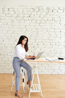 Une belle jeune femme afghane en tenue d'affaires élégante est assise devant une table devant un ordinateur portable avec des tableaux et des graphiques.
