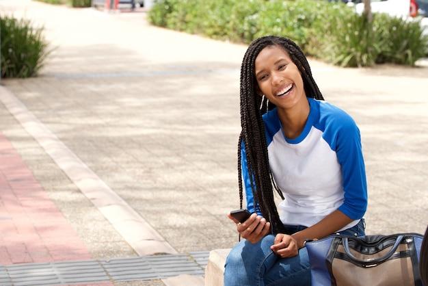 Belle jeune femme africaine assis à l'extérieur avec un téléphone intelligent et souriant