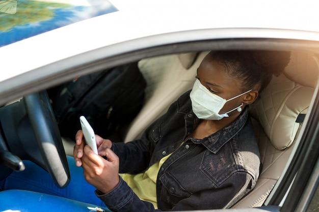 Belle jeune femme africaine au volant d'une voiture en masque médical