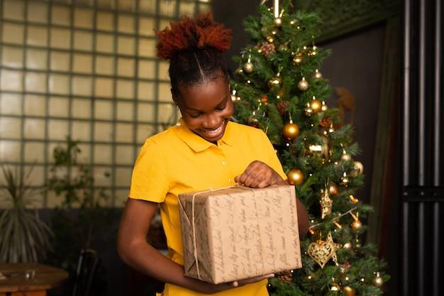 Belle jeune femme africaine avec un cadeau près de l'arbre de noël