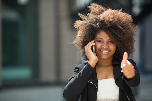 Belle jeune femme africaine avec une coiffure volumineuse avec téléphone portable