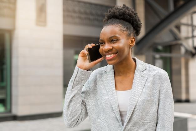 Belle jeune femme africaine dans une veste près du bâtiment
