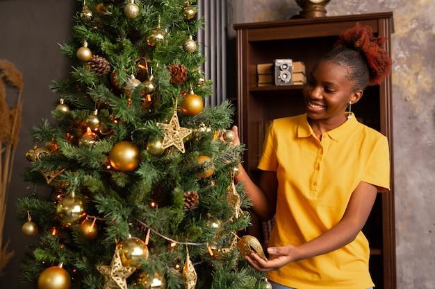 Belle jeune femme africaine décore un arbre de noël pour noël
