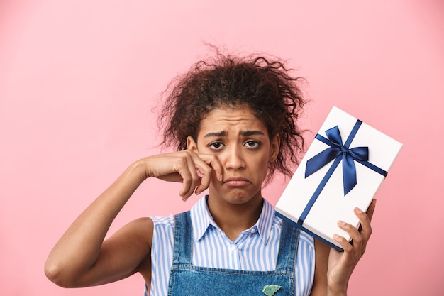 Belle jeune femme africaine déçue tenant une boîte-cadeau sur rose