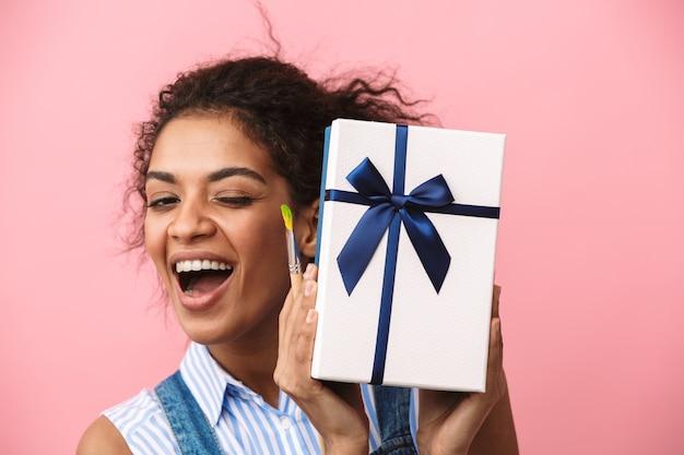 Belle jeune femme africaine excitée tenant une boîte-cadeau sur rose