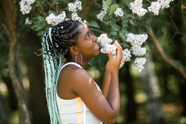 Belle jeune femme africaine avec des fleurs de printemps sur l'arbre
