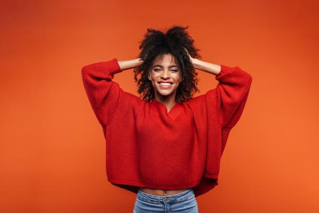 Belle jeune femme africaine joyeuse portant un pull debout isolé sur un mur rouge, posant, jouant avec les cheveux
