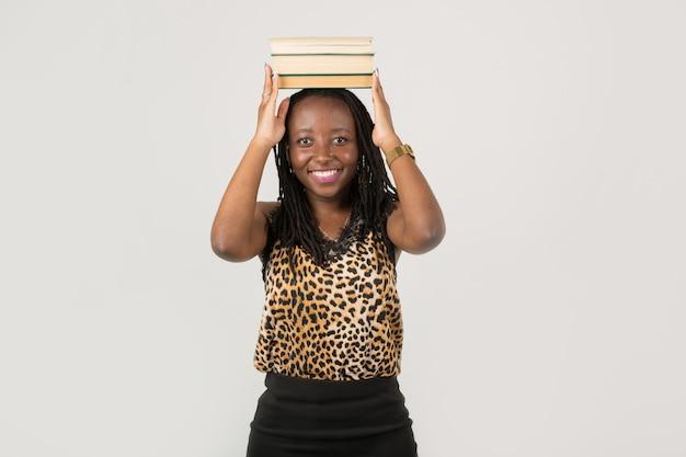 Belle jeune femme africaine avec des livres sur sa tête