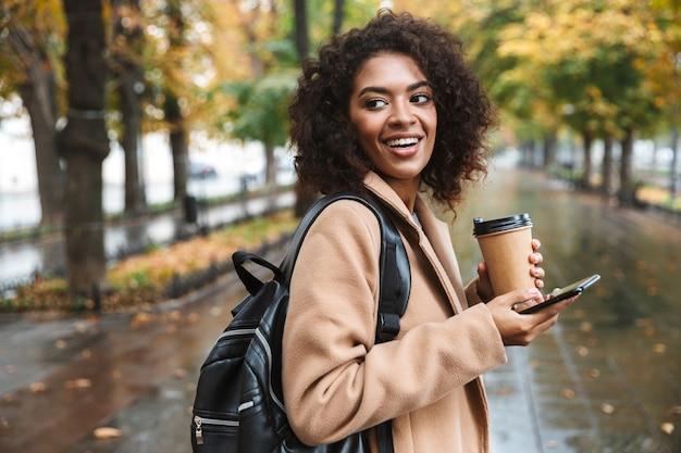 Belle jeune femme africaine portant manteau marchant à l'extérieur dans le parc, transportant un sac à dos, à l'aide de téléphone portable, boire du café