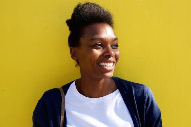 Belle jeune femme africaine regarder loin et sourire