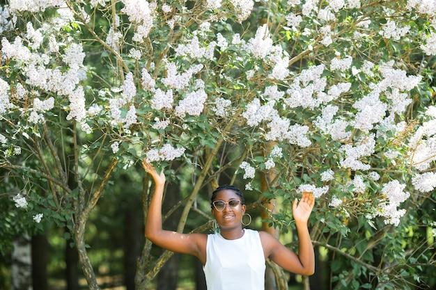 Belle jeune femme africaine en robe blanche portant des lunettes de soleil