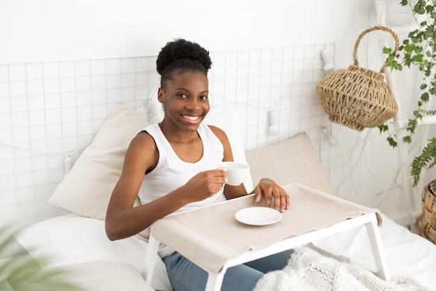 Belle jeune femme africaine se trouve sur un lit blanc